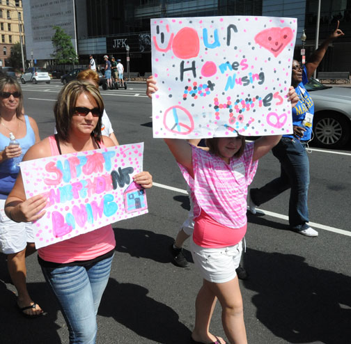 Two NCIL Members carry signs - Our Homes Not Nursing Homes and Support Independent Living