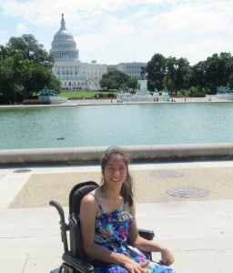 Angela West poses for a photo in front of the United States Capitol - she is wearing a purple flower dress and sitting in her wheelchair