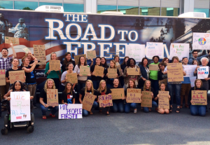 Students at Millersville University gather in front of the ADA bus with dozens of different protest signs