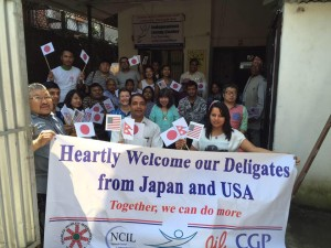 Nepalese Delegation of 23 people hold American and Japanese and Neopalese flags and a banner that reads Heartly Welcome our Deligates from Japan and USA - Together we can do more