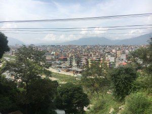 View of Kathmandu - a bustling city with multi-colord buildings and mountains in the distance