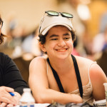 Three young people smile while sitting together at a table at the 2016 Annual Conference on Independent Living