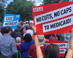 Approximately 50 people are gathered for a Rally. Several people have signs that read No Cuts No Caps to Medicaid - ACLU