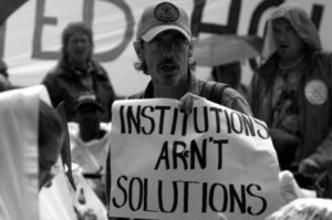 "A black and white photo of a person carrying a sign that reads ""Institutions Aren't Solutions"""