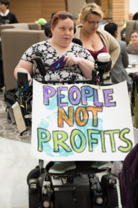 "A NCIL member holds a sign that reads ""People Not Profits"" at the 2017 Annual Conference on Independent Living"